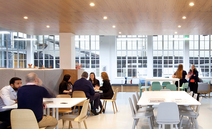 Spaces members working and conversating in a coworking space, the Business club.