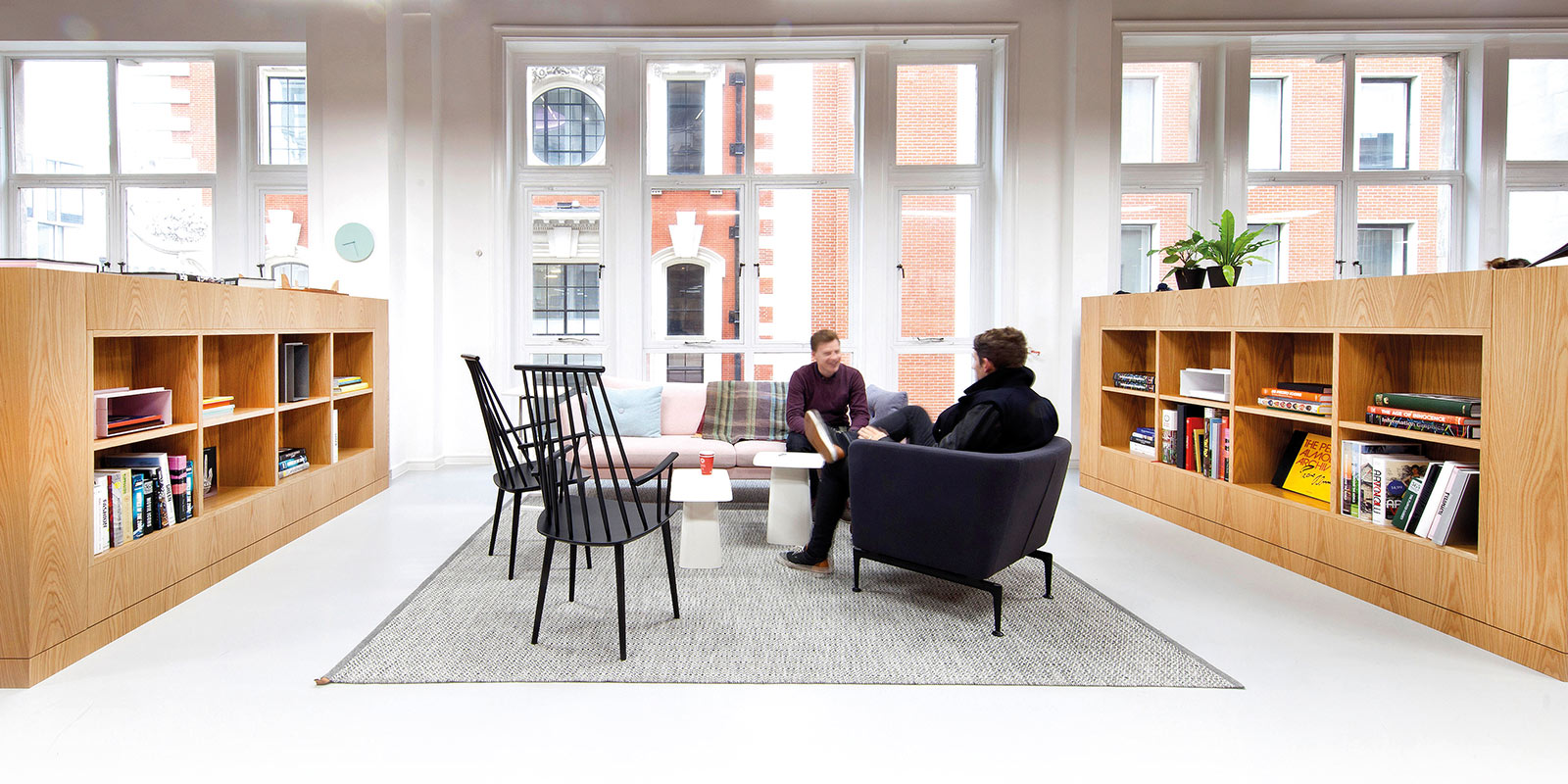 Spaces users chatting in the coworking space with designer furniture and meeting rooms to rent.