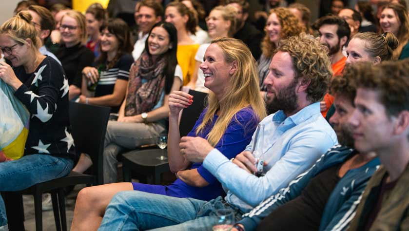 People in a crowd laughing in a designer conference room