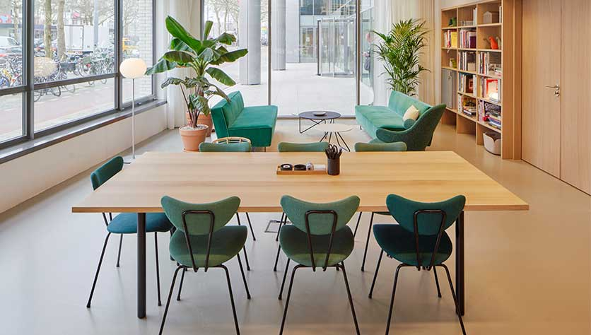 green chairs in a beautiful office space for a blogpost about how to spice up your desk life