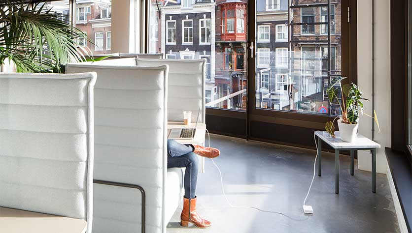 Woman sitting in lounge chair at spaces vijzelstraat with view on canal houses