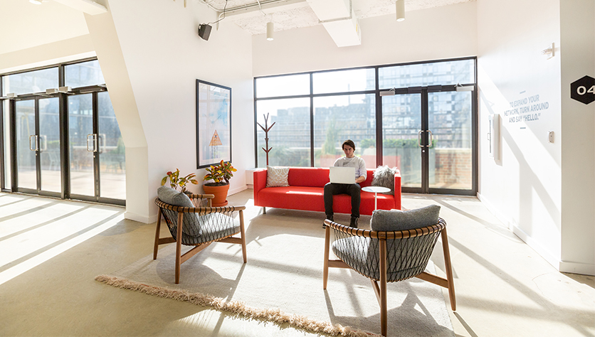 man working on sofa in light open space